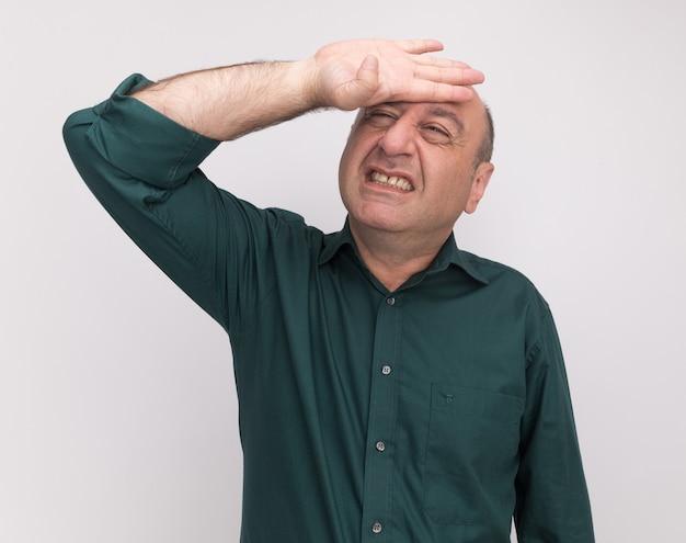 Rammaricato alzando lo sguardo uomo di mezza età che indossa la maglietta verde mettendo la mano sul tempio isolato sul muro bianco