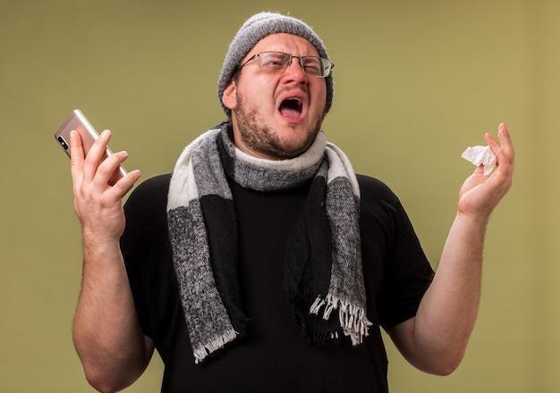 冬の帽子とスカーフを持った電話を身に着けている後悔した中年の病気の男性