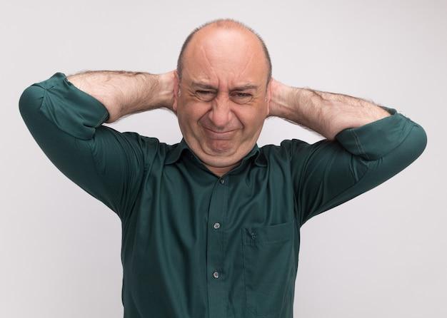 Сожалеющий мужчина средних лет в зеленой футболке, положив руку за голову, изолированную на белой стене