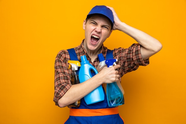 Regretted putting hand on head young cleaning guy wearing uniform and cap holding cleaning tools