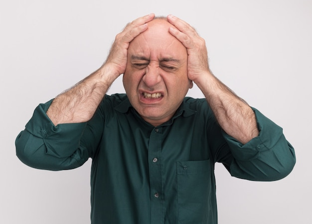 Regretted with closed eyes middle-aged man wearing green t-shirt grabbed head isolated on white wall