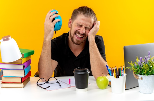 Regretted with closed eyes young guy student sitting at table with school tools holding alarm clock