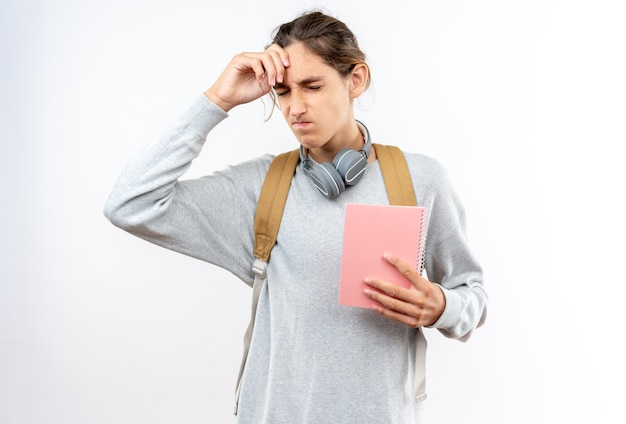 Regretted with closed eyes young guy student wearing backpack with headphones on neck holding notebook putting hand on forehead