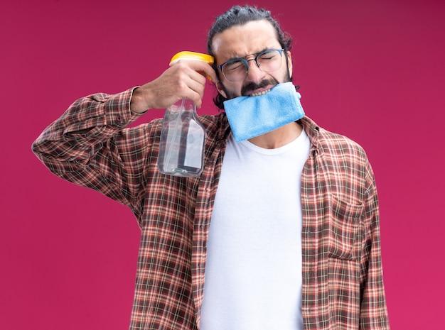 눈을 감고 젊은 잘 생긴 청소 남자 입에 걸레를 들고 분홍색 벽에 고립 된 사원에 스프레이 병을 넣어 입고