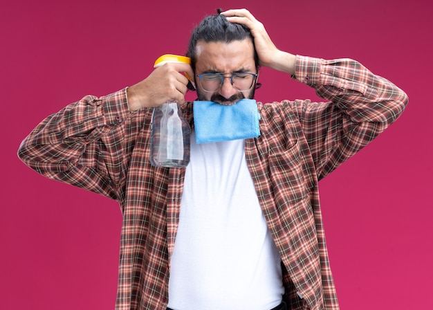 Regretted with closed eyes young handsome cleaning guy wearing t-shirt holding rag in mouth and putting spray bottle on temple isolated on pink wall