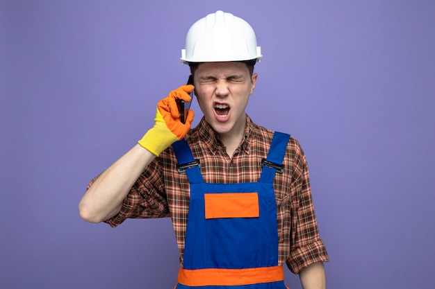 Regretted with closed eyes young male builder wearing uniform with gloves speaks on phone