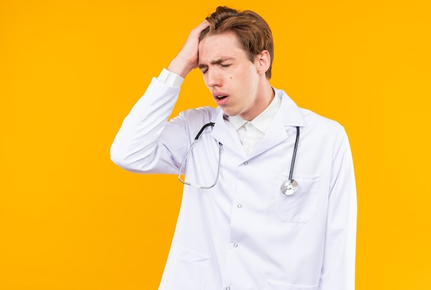 Regretted with closed eyes young male doctor wearing medical robe with stethoscope putting hand on head isolated on orange wall