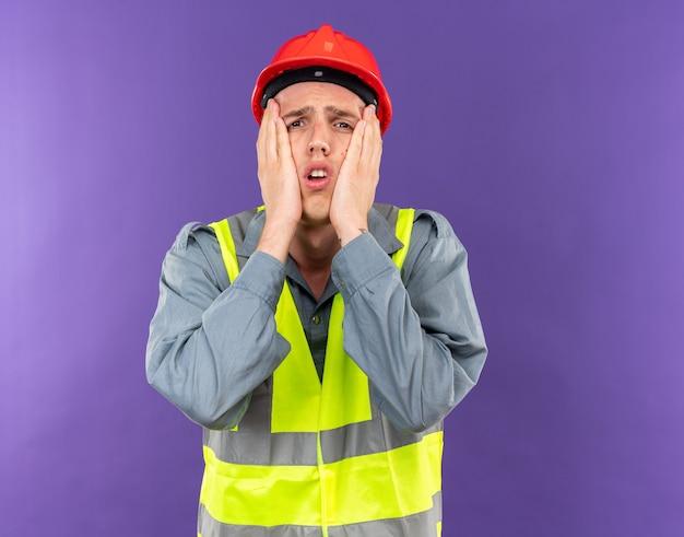 Сожалеет молодой строитель человек в униформе, положив руки на щеки