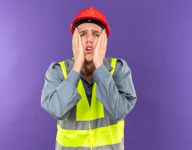 Regretted young builder man in uniform putting hands on cheeks