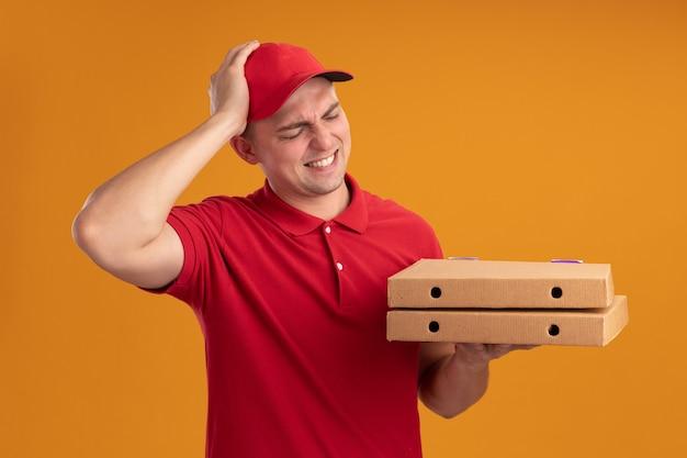 Rammaricato giovane uomo di consegna che indossa l'uniforme con cappuccio che tiene e guardando le scatole per pizza mettendo la mano sulla testa isolata sulla parete arancione