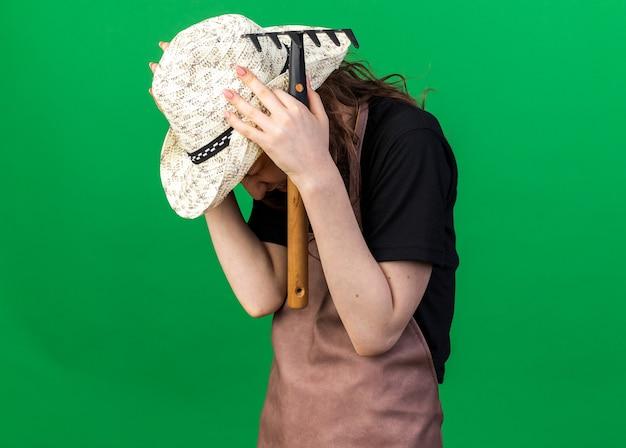 熊手をつかんだ頭を持っている園芸帽子をかぶっている後悔した若い女性の庭師