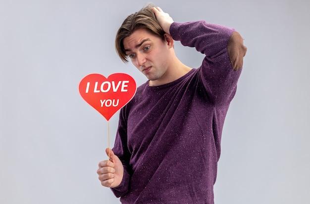 バレンタインデーに赤いハートを棒に抱いて後悔している若い男は、白い背景で隔離の頭に手を置くテキストを愛しています