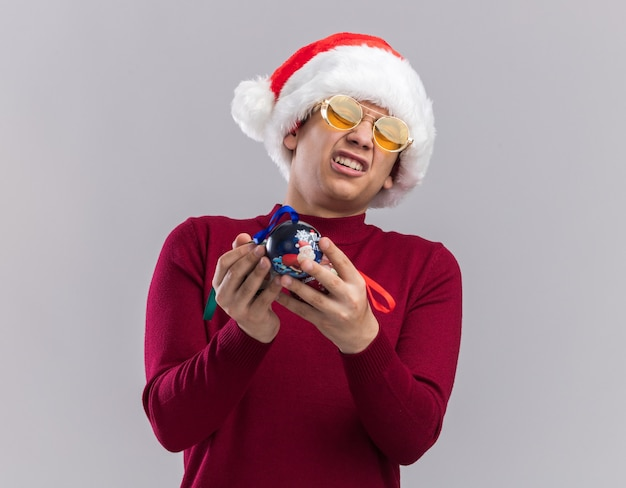 흰색 배경에 고립 된 크리스마스 트리 볼을 들고 안경 크리스마스 모자를 쓰고 유감 젊은 남자