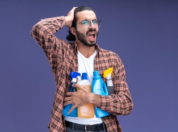 파란색 벽에 고립 된 머리에 손을 넣어 청소 도구를 들고 티셔츠를 입고 유감 젊은 잘 생긴 청소 남자