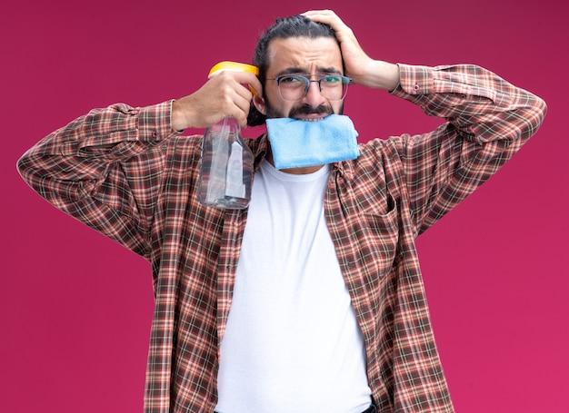 입에 걸레를 들고 분홍색 벽에 고립 된 머리에 손을 넣어 사원에 스프레이 병을 넣어 티셔츠를 입고 유감 젊은 잘 생긴 청소 남자