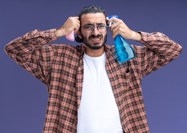Regretted young handsome cleaning guy wearing t-shirt holding spray bottle with rag around face isolated on blue wall