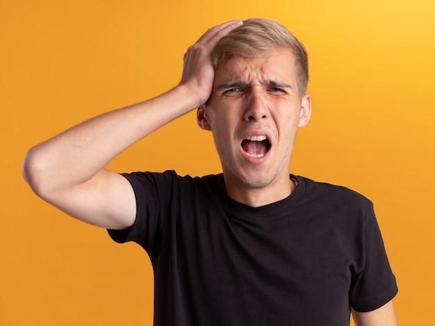 Rammaricato giovane bel ragazzo che indossa la camicia nera ha afferrato la testa isolata sul muro giallo