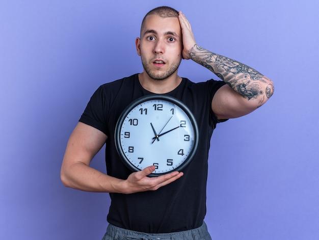 Deplorato giovane bel ragazzo che indossa una maglietta nera che tiene l'orologio da parete che mette la mano sulla testa isolata sul muro blu