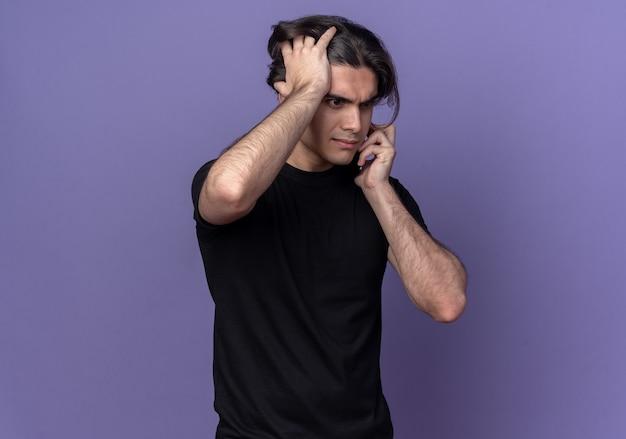 Жалкий молодой красивый парень в черной футболке разговаривает по телефону и схватился за голову, изолированную на фиолетовой стене