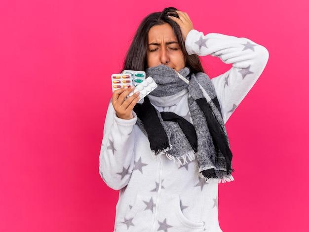 Rammaricato giovane ragazza malata con gli occhi chiusi che indossa e ha coperto la bocca con la sciarpa che tiene le pillole e mettendo la mano sulla testa isolata sul colore rosa