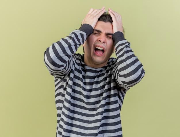 Rammaricato giovane uomo malato ha afferrato la testa isolata su verde oliva