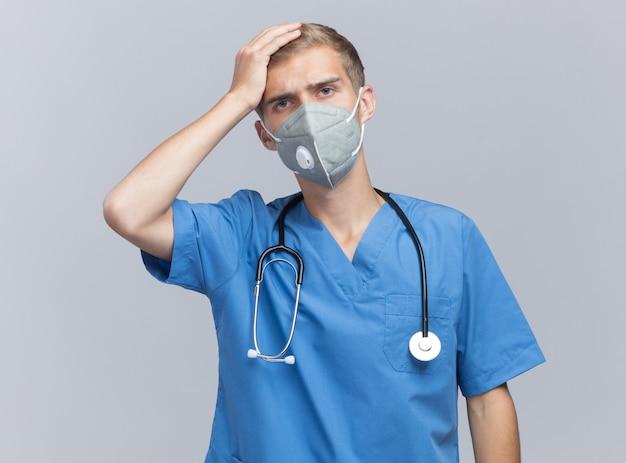 청진 기 및 의료 마스크 흰 벽에 고립 된 머리에 손을 넣어 의사 유니폼을 입고 유감 젊은 남성 의사