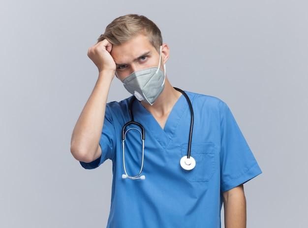 Rammaricato giovane medico maschio che indossa l'uniforme del medico con lo stetoscopio e la mascherina medica che mette la mano sulla testa isolata sulla parete bianca