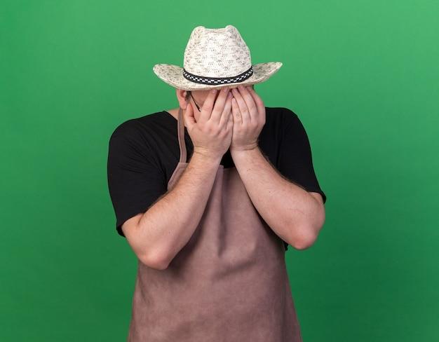 緑の壁に隔離された手でガーデニング帽子で覆われた顔を身に着けている後悔の若い男性の庭師