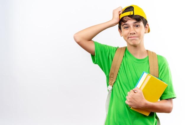 白い壁に隔離された額に手を置く本を保持しているキャップとバックパックを身に着けている後悔の少年