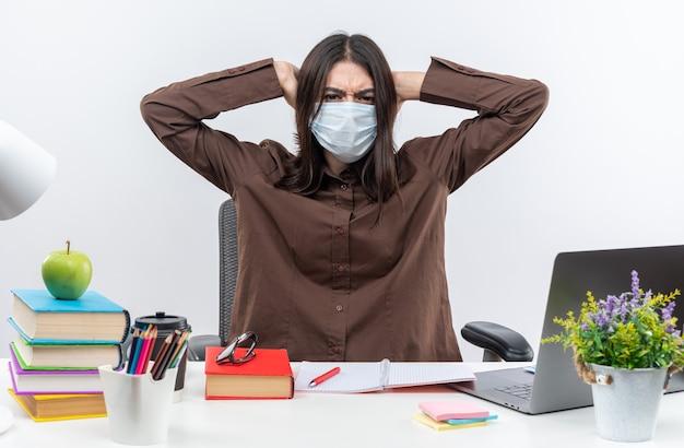 의료용 마스크를 쓴 유감스러운 젊은 여학생이 학교 도구로 머리를 움켜쥐고 탁자에 앉아 있다