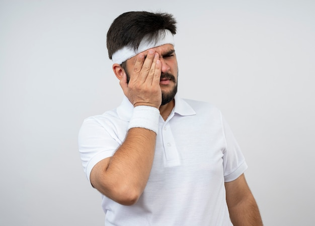 Regretted young sporty man looking at side wearing headband and wristband covered eye with hand isolated on white wall