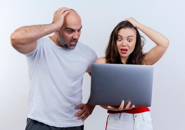 Rimpiangendo le coppie adulte sia mettendo la mano sul computer portatile capo della tenuta della donna che lo esaminano