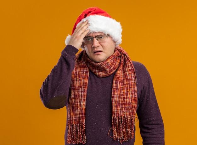 Rammarico uomo adulto con gli occhiali e cappello santa con sciarpa intorno al collo mettendo la mano sulla testa guardando il lato isolato su sfondo arancione
