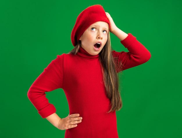 빨간 베레모를 쓴 어린 금발 소녀가 녹색 벽에 격리된 입을 벌리고 머리와 허리에 손을 대고 올려다보는 것을 유감스럽게 생각합니다.