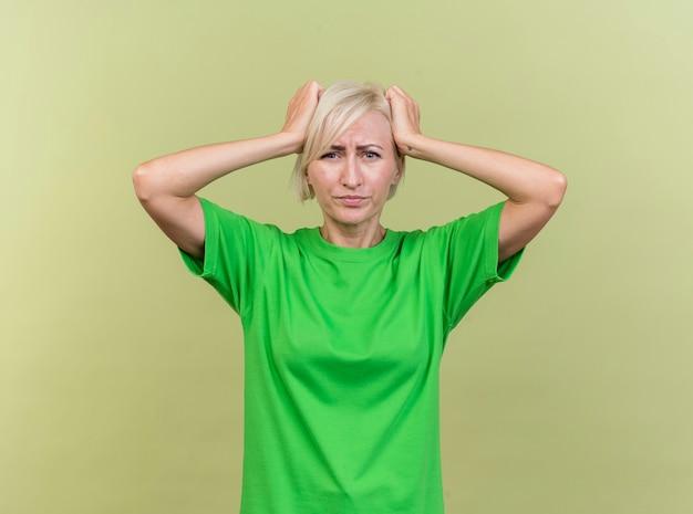 올리브 녹색 배경에 고립 된 머리를 들고 카메라를보고 유감 중년 금발 슬라브 여자