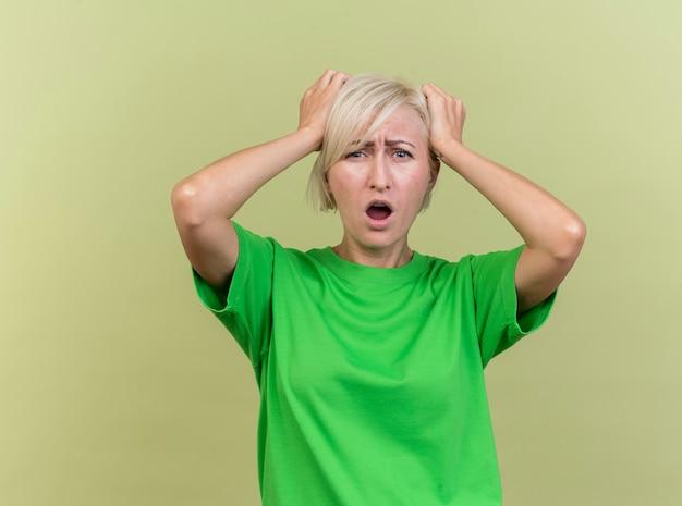 복사 공간 올리브 녹색 배경에 고립 된 머리에 손을 댔을 카메라를보고 유감 중년 금발 슬라브 여자