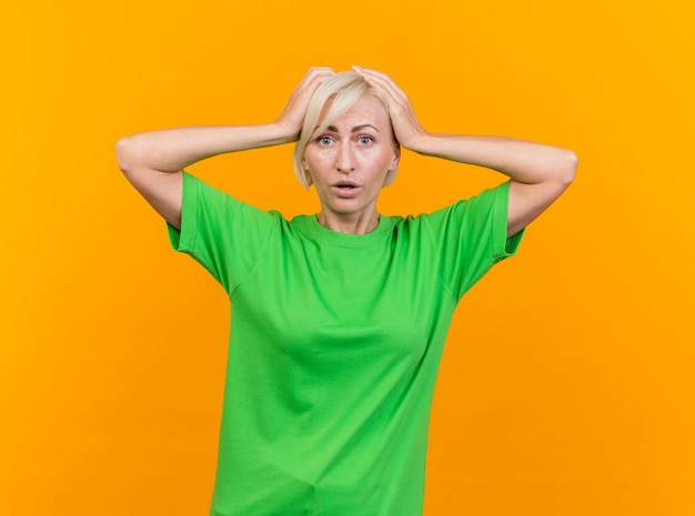 Rammarico donna slava bionda di mezza età che guarda l'obbiettivo mantenendo le mani sulla testa isolata su sfondo giallo