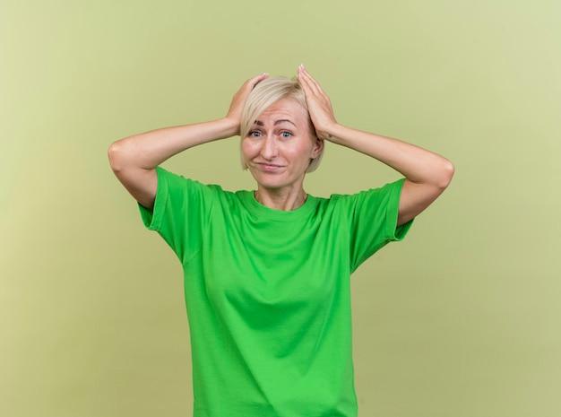 Deplorando la donna slava bionda di mezza età che guarda davanti mantenendo le mani sulla testa isolata sulla parete verde oliva