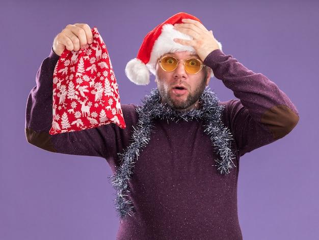 Rimpiangere l'uomo di mezza età che indossa il cappello della santa e la ghirlanda di orpelli intorno al collo con gli occhiali che tengono il sacco del regalo di natale tenendo la mano sulla testa isolata sul muro viola