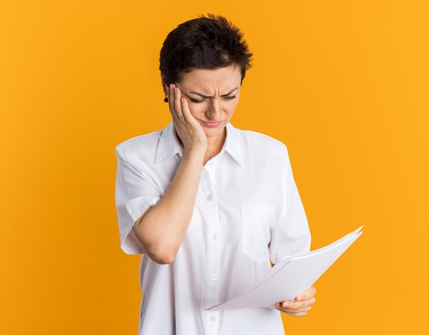 Regretting middle-aged woman holding and looking at documents keeping hand on face