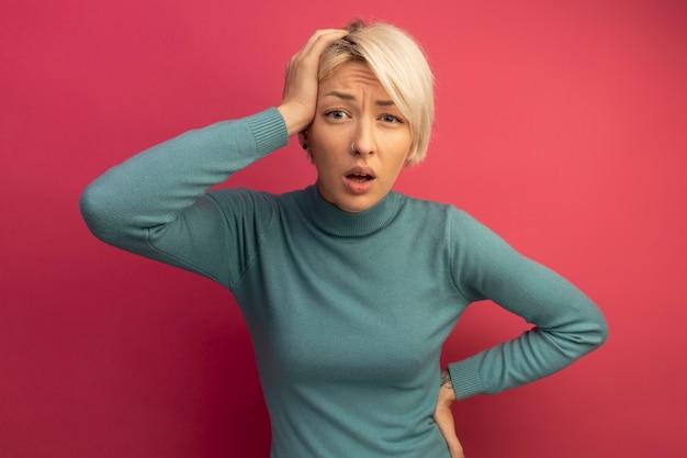 머리에 손을 얹고 분홍색 벽에 고립된 채 허리에 또 다른 손을 얹은 것을 유감스럽게 생각하는 어린 금발 소녀