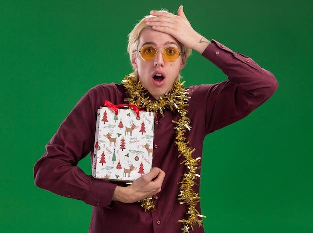 Сожалеющий молодой блондин в очках с гирляндой из мишуры на шее, держащий рождественский подарочный пакет, держа руку на голове, изолированную на зеленой стене