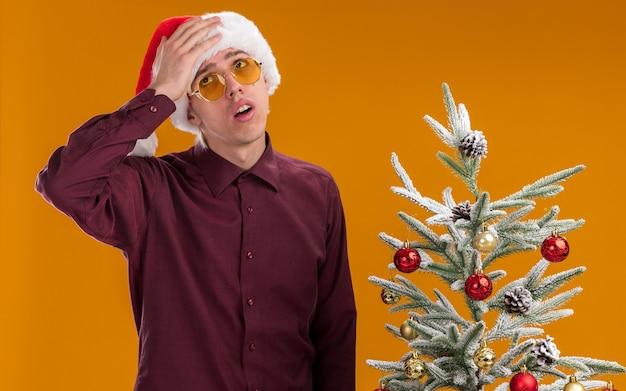 Сожалеющий молодой блондин в шляпе санта-клауса и очках, стоящий возле украшенной елки, глядя вверх, держа руку на голове, изолированную на оранжевом фоне
