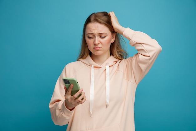 Rimpiangendo la giovane donna bionda mantenendo la mano sulla testa tenendo e guardando il telefono cellulare
