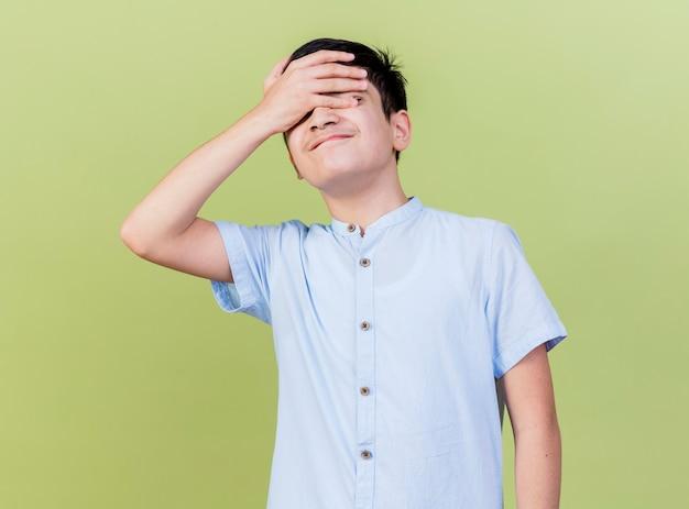 올리브 녹색 벽에 고립 된 닫힌 눈으로 이마에 손을 유지하는 어린 소년을 유감