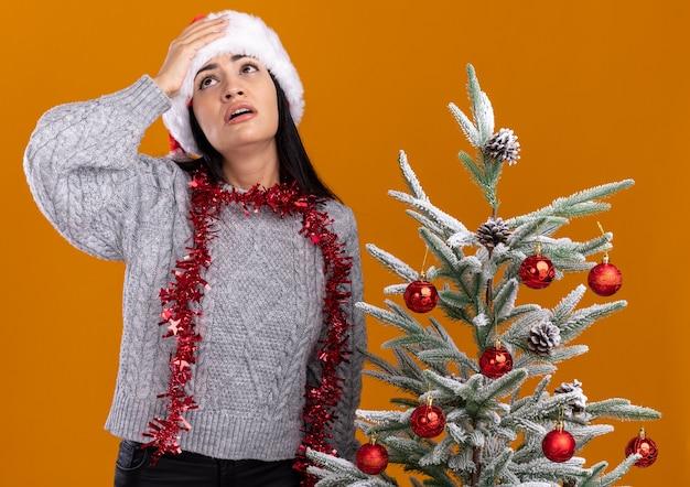 Rimpiangendo la giovane ragazza caucasica che indossa il cappello di natale e la ghirlanda di orpelli intorno al collo in piedi vicino all'albero di natale decorato tenendo la mano sulla testa guardando in alto isolato sul muro arancione