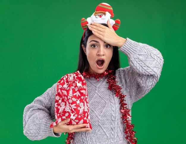 Regretting young caucasian girl wearing santa claus headband and tinsel garland around neck holding christmas gift sack  keeping hand on forehead isolated on green wall