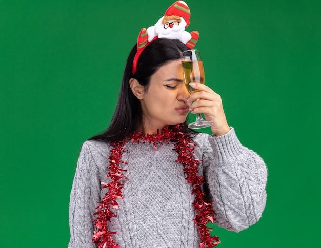 Rimpiangendo la giovane ragazza caucasica che indossa la fascia di babbo natale e la ghirlanda di orpelli intorno al collo che tiene un bicchiere di champagne toccando la fronte con gli occhi chiusi isolati su priorità bassa verde