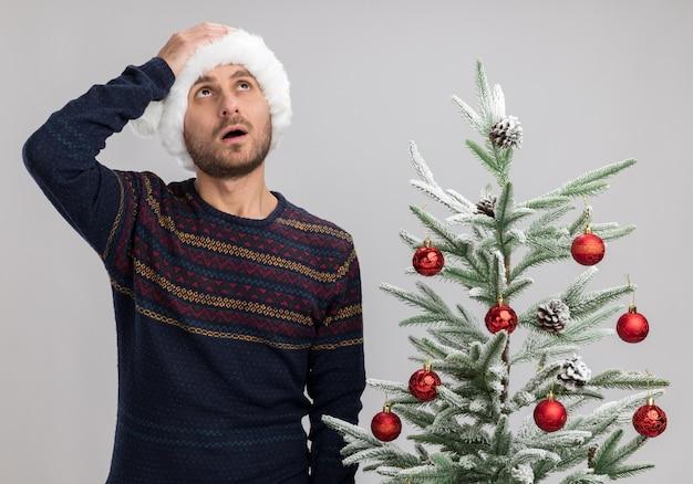 Rimpiangendo il giovane uomo caucasico che indossa il cappello di natale in piedi vicino all'albero di natale che osserva in su tenendo la mano sulla testa isolata su fondo bianco