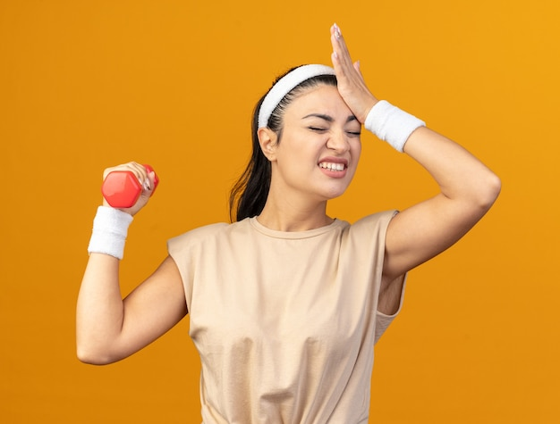머리띠와 팔찌를 착용한 백인 스포티 소녀가 주황색 벽에 격리된 눈으로 머리에 손을 대고 덤벨을 들고 있는 것을 유감스럽게 생각합니다.